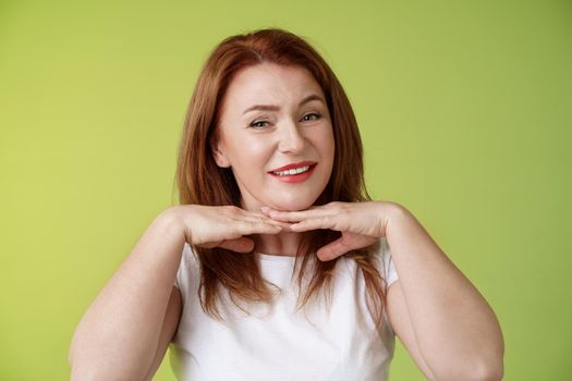 Looking good. Happy cheerful redhead middle-aged 50s woman smiling delighted hold hands under chin accept flaws blemished like own skin condition apply aging creme cosmetics green background