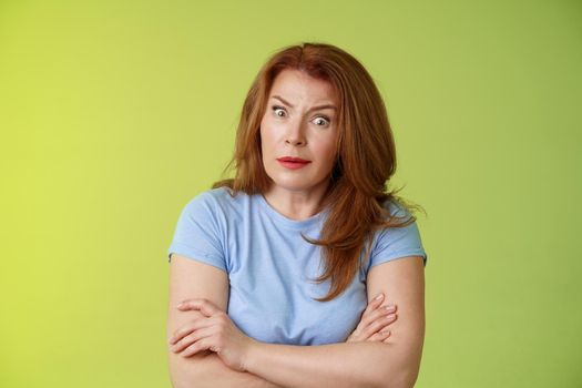You did what. Confused shocked speechless redhead mature mother stare camera puzzled concerned cross arms chest self-soothing bothered pose look questioned hesitant green background
