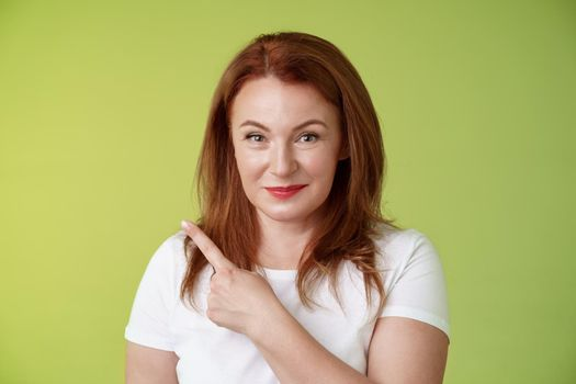 Kind cheerful good-looking middle-aged woman 50s redhead white t-shirt smiling modest assured give advice pointing upper left corner indicating great promotion advertising product green background