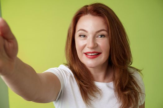 Close-up joyful enthusiastic redhead alluring middle-aged woman extand arm towards camera taking selfie smartphone smiling broadly posing photograph taking picture device green background