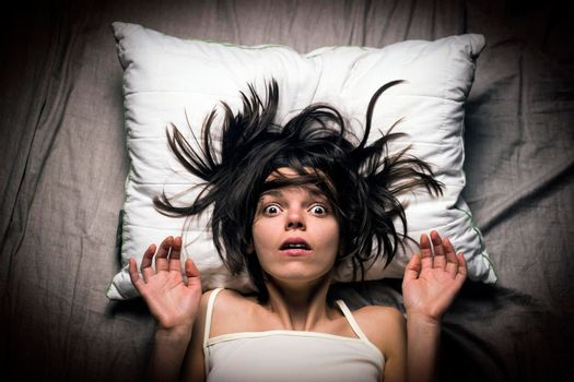 Young girl with a frightened expression wakes up from a nightmare in bed.
