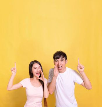 Excited young couple screaming and pointing up