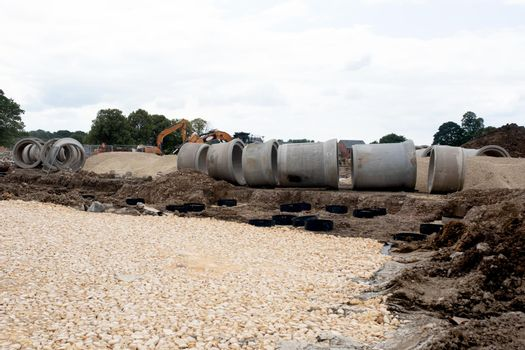 Big diameter concrete drainage pipe on new housing and road development site ready to be installed undeground to form drainage system and attenuation tank to store excess of storm rain water to prevent flooding of the estate.