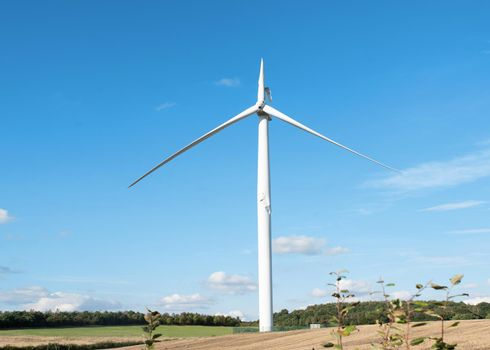 Electricity power wind turbine with broken blade and damaged tower awaiting repair after accident.