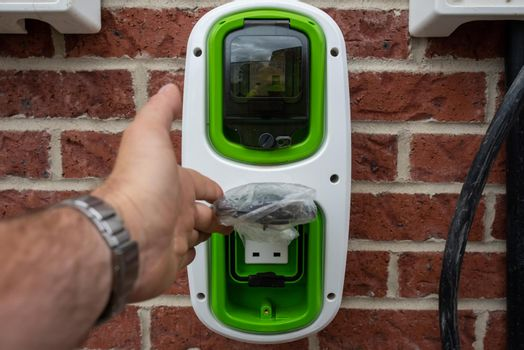 Electric vehicle domestic charging point installed outside of the house on new housing development as part of green energy program to allow recharging vehicle overnight