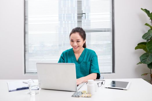 A female doctor working on medical expertise while sitting at desk in front of laptop