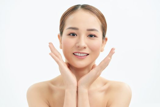 Beautiful young Asian woman with fresh clean skin that touches her face with both hands. Spa, cosmetology and beauty.