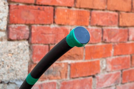 Water supply polyethylene pipe with a plug on the background of a brick wall. Plumbing in a country house