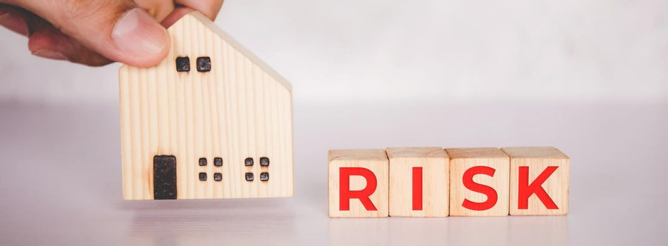 Planning with finance and investment of business about real estate with risk and safety of insurance, uncertainty for economy, hands put home and cube wooden block with word RISK, business concepts.