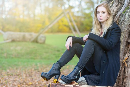 Young girl is sitting in autumn park