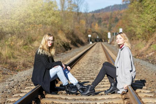 Two girls are sitting on rail and looking at the camera