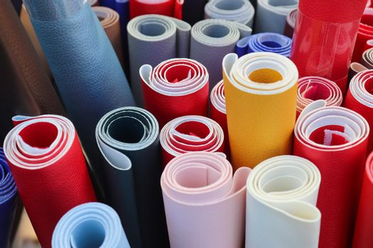 Close up view on rolled samples of cloth and fabrics in different colors found at a fabrics market..