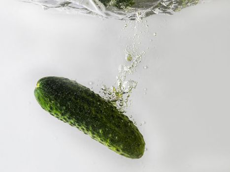 green cucumber falls into the water scattering a lot of sprays and drops