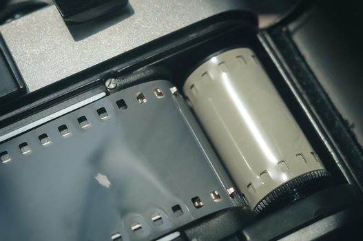 Close-up of the back of the Soviet film camera with the lid of the film compartment open. Dark background, copy space, deep shadows, horizontal composition