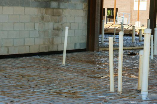 Plastic vapor barrier on slab with plumbing pvc pipes of foundation