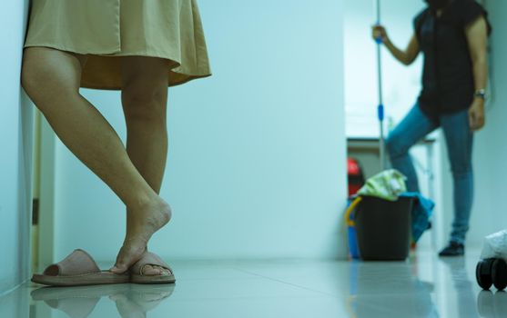 Closeup woman leg with hair need hair laser removal and skin treatment. Woman with hairy legs standing in the office on a blurred woman with mop and bucket for cleaning the floor. Woman wear slippler.