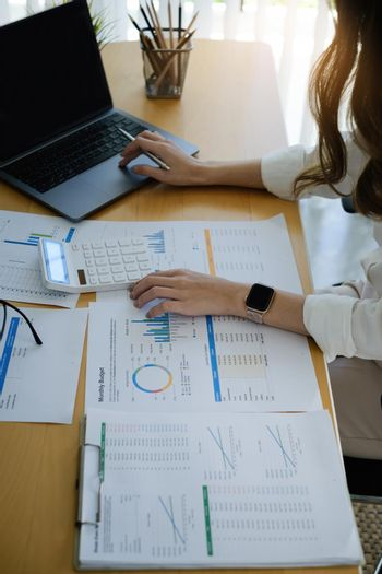 A female investment consultant examines the yearly financial report of a corporation. Stock market, office, tax concept.