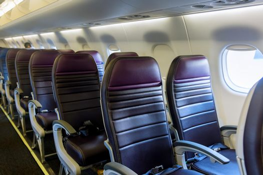 Aircraft interior. The cabin of modern passenger plane. Aircraft seats and window.