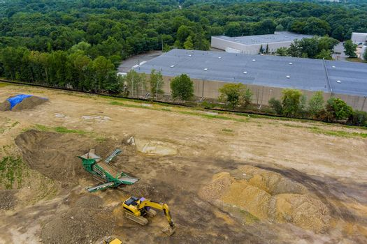 Aerial drone of a construction site with heavy equipment is grading the land, moving flattening