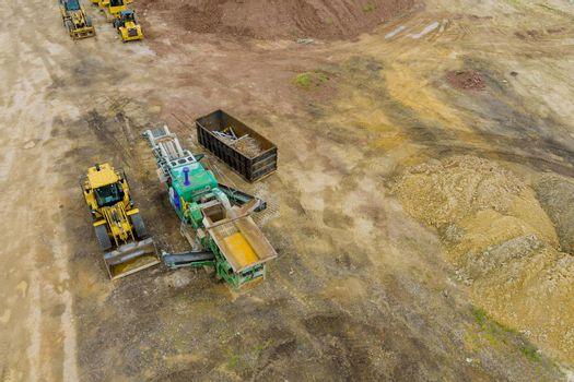 Trucks and heavy machinery clearing the land for the construction