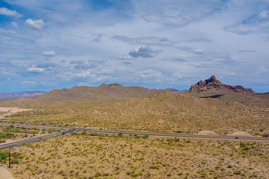 Aerial view rock mountains in the high desert in the middle of the highway of Arizona