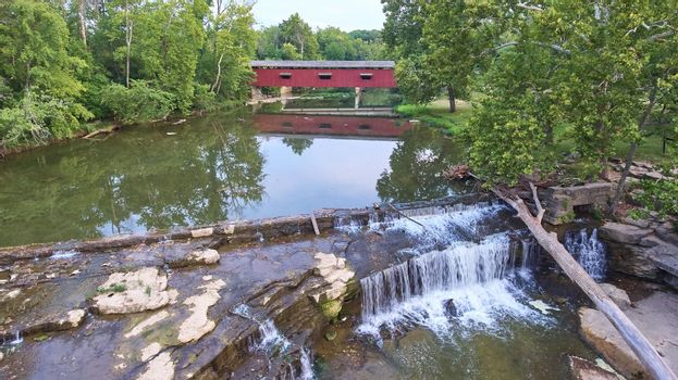 Waterfall at Cataract Falls with a fallen tree collapsed over it and a covered bridge in the background