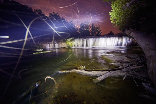 Trails of ghostly lights at dusk near waterfalls at Cataract Falls