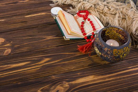 Lighted candle holder; kuran and red prayer beads on wooden desk Picture on pik. High quality beautiful photo concept