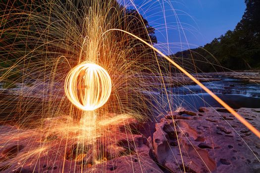 Yellow orbs of sparks flying into craggy stone and rock in front of waterfalls at Cataract Falls