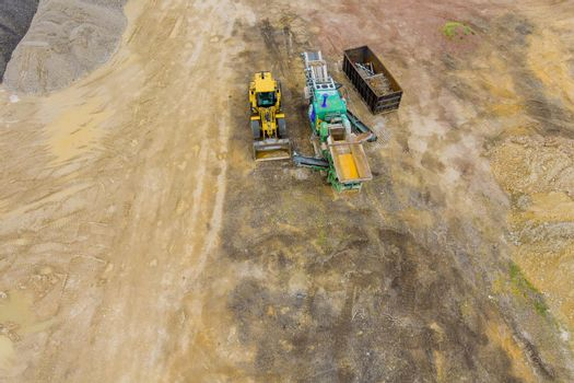 Construction heavy equipment is grading the land, moving out clay soil