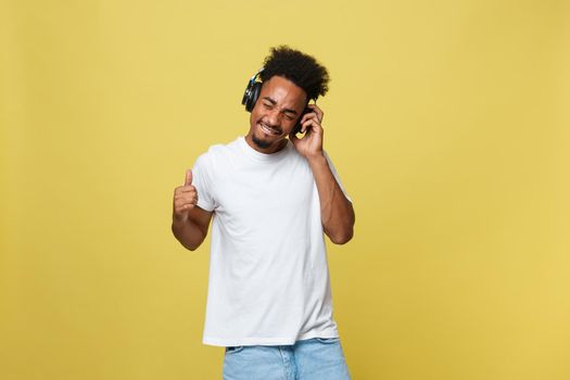 Portrait good-looking african male model with beard listening to music. Isolated over yellow background