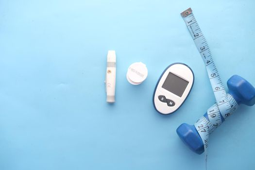 diabetic measurement tools and a dumbbell on blue background