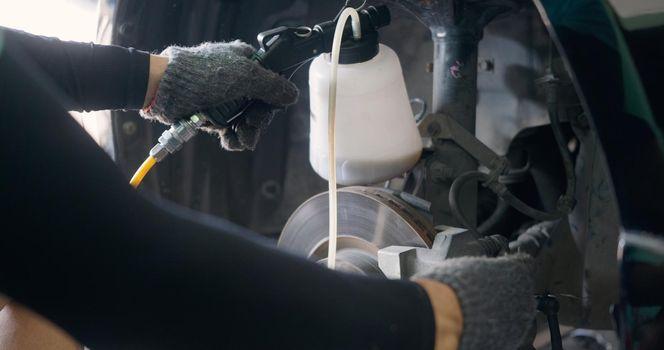 Auto mechanic replacing brake fluid on a vehicle