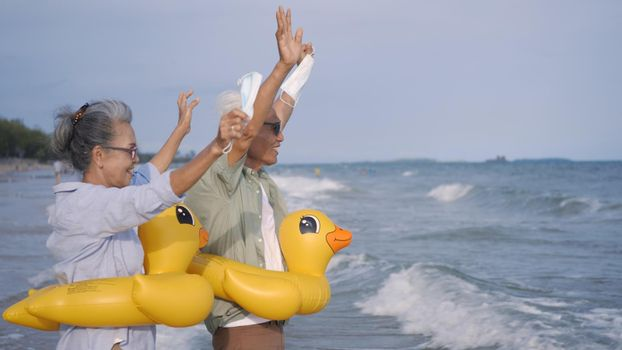 senior couple wear rubber ring take off medical face mask and running to the beach enjoying life