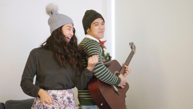 man and woman playing the guitar, singing song and dancing together