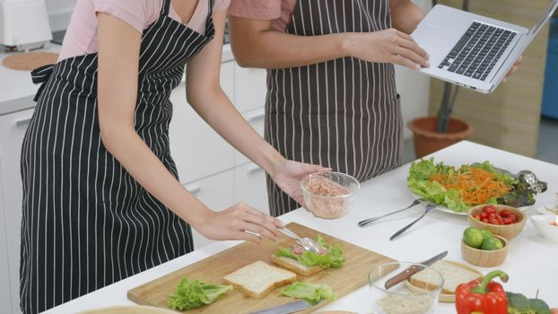 couple husband and wife cooking food vegetable salad in kitchen together at home