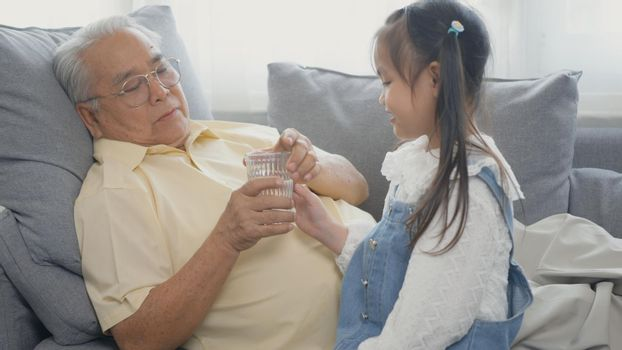 granddaughter brought glass of water for grandpa to eat on the sofa in the living room