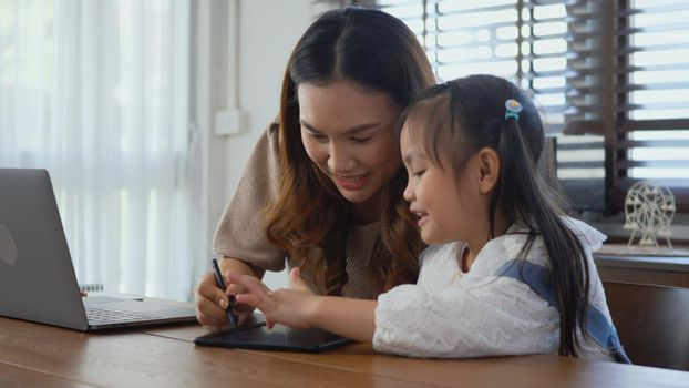 mother working with laptop computer at home and help daughter doing homework