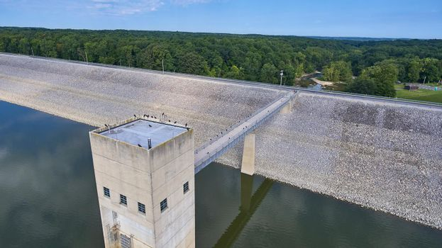 Aerial of a concrete dam with gravel slopes and crows on the rood and on the bride and a forest in the background