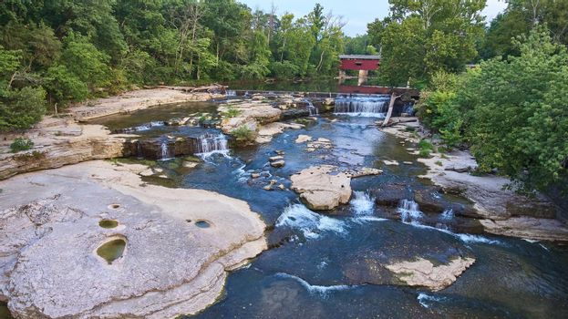 Multiple waterfalls aerial shot at the Cataract Falls with a covered bridge in the background