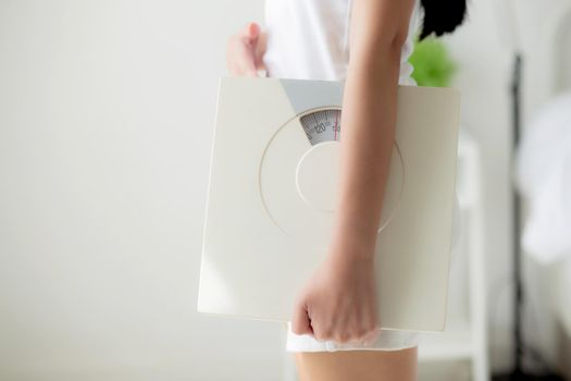 Closeup hands of woman holding scales with confident with control and weightloss of success, girl dieting for result of weight loss with satisfied, one person, healthy and lifestyles concepts.