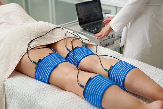The procedure of myostimulation on legs of a woman in a beauty salon. Caring for the body with electrostimulation, reducing excess weight