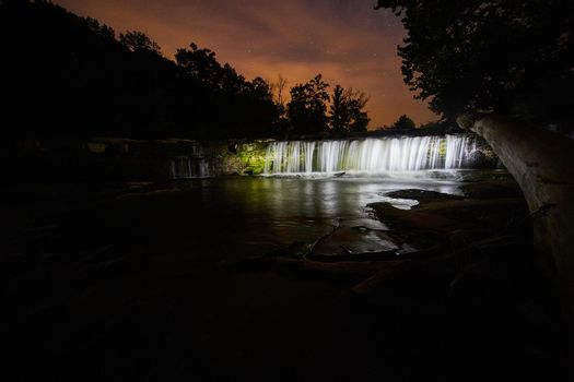 Glowing white waterfalls at night under a star filled sky at Cataract Falls