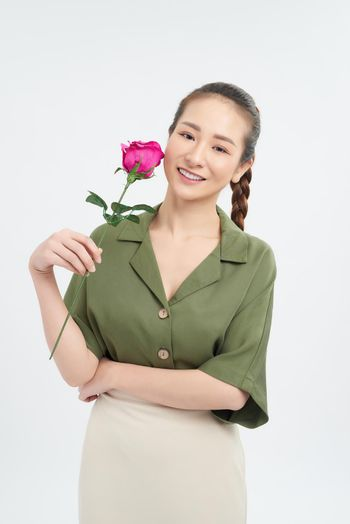 Young woman holding a single stem rose