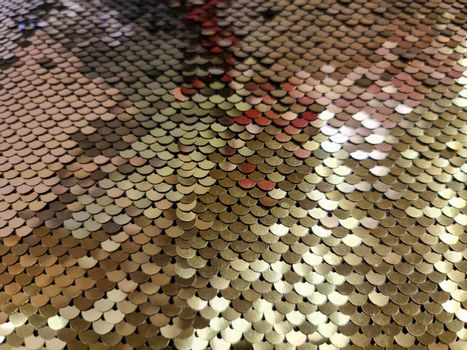 Close up view on samples of sequin fabric in golden colors