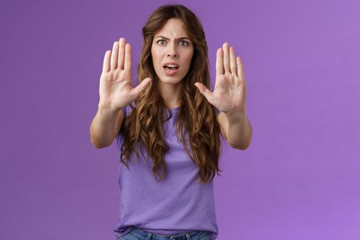 You need stop hold it. Serious-looking intense displeased woman pull hands prohibition taboo sign frowning demand enough shooting me bad mood restict doing mistake purple background