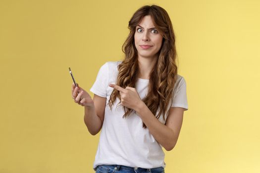 Girl answers strange weird call receive crazy upsetting message cringe doubtful displeased smirking dismay pointing suspicious smartphone stand yellow background intense frustrated