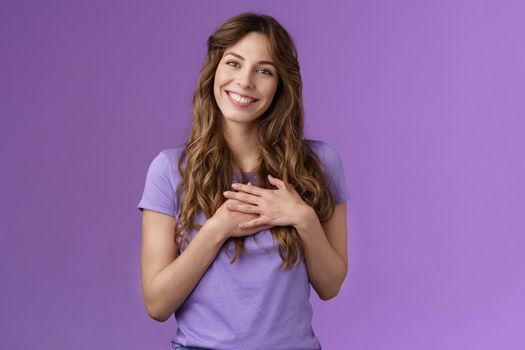 Tender charming grateful lovely curly-haired girl feel delighted sympathy touch heart cherish cute heartwarming date smiling broadly stand purple background joyful grateful appreciate effort
