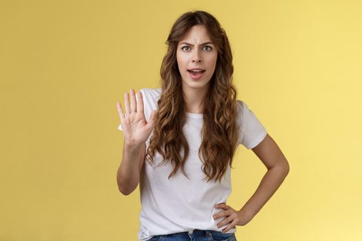 Hold it stop. Girl feeling intense serious grimacing demand end unpleasant conversation raise palm rejection refusal prohibit enough wasting my time frowning disappointed yellow background