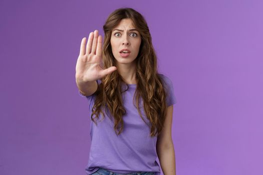 Worried shocked curly-haired woman gasping stare camera anxiously pull hand stop sign begging end prohibiting friend drive after drinking stand purple background forbid warn you purple background